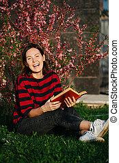 śmiech, głośny, portret, książka, hands., młody, poza, kobieta, na wolnym powietrzu