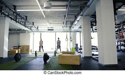atak, para, wykonując, młody, kettlebells., sala gimnastyczna
