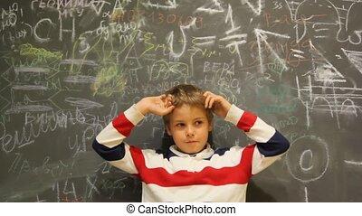 chłopiec, stoi, zaintrygowany, przeciw, pisanie, chalkboard, pokryty