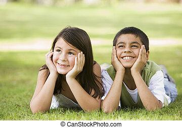 focus), park, młody, dwa, outdoors, (selective, uśmiechanie się, dzieci, leżący
