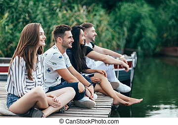 grupa, odprężając, molo, młody, rzeka, przyjaciele, szczęśliwy