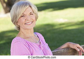 kobieta posiedzenie, zewnątrz, uśmiechanie się, senior, szczęśliwy