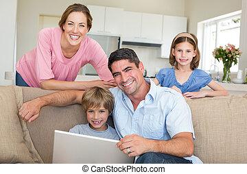 laptop, posiedzenie, używając, uśmiechanie się, rodzinny pokój