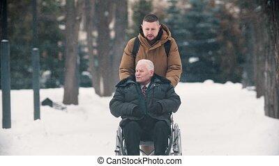 outdoors, młody mężczyzna, jego, pieszy, wheelchair, dziadek