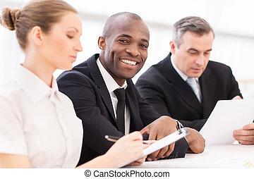 patrząc, koledzy, jego, handlowy, posiedzenie, meeting., młody, razem, radosny, znowu, aparat fotograficzny, formalwear, afrykanin, uśmiechnięty człowiek