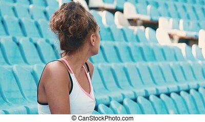 piękny, tribunes, kobieta posiedzenie, młody, lekkoatletyka, stadium., widok budynku