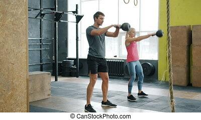 ruch, młody, poza, powolny, sala gimnastyczna, wykonując, kettlebells, para, kucki, pracujący