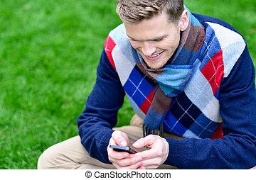 ruchomy, park, telefon, używając, uśmiechnięty człowiek, szczęśliwy