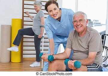 senior, pomagając, terapeuta, samica, człowiek, dumbbells