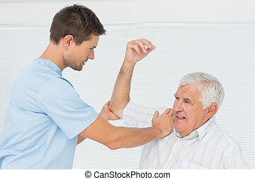 senior, ręka, pomagając, jego, człowiek, napinać, fizykoterapeuta