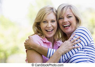 uśmiechanie się, kobiety, dwa, tulenie, outdoors